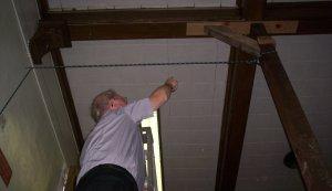 Deacon Bill Archer indicates damage to St. Michael's parish hall